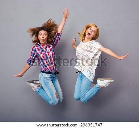 Two cheerful girls jumping over gray background