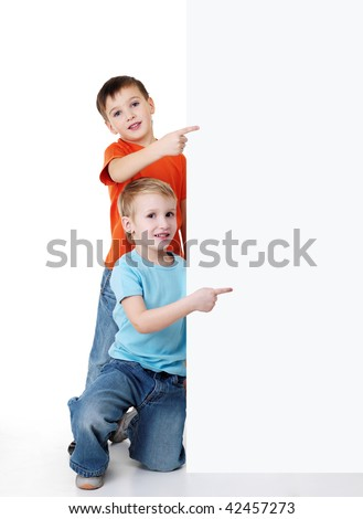 Two cheerful little boys look outs from the billboard and pointing on it. Fill-length portrait