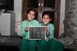 Two Cheerful Little girl sitting on the Cot at their home holding chalkboard (slate) with English alphabet writing on it, wearing school dress and laughing together portrait.