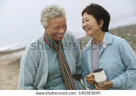 Two cheerful middle aged female friends talking on the beach #140383849