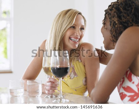 Two cheerful multiethnic women with red and white wine sitting at the table