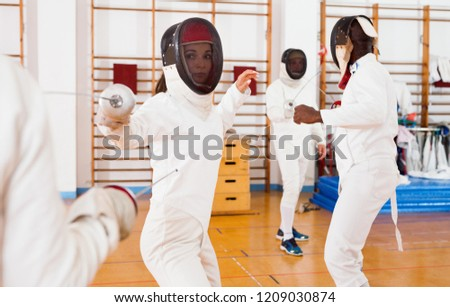 Two  cheerful positive smiling female fencers  exercising movements in duel at fencing room