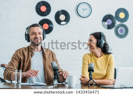 two cheerful radio hosts in headphones recording podcast in studio together