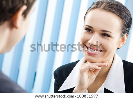 Two cheerful smiling young businesspeople, or business woman and client, working at office