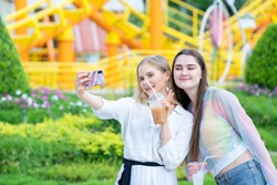 Two cheerful teenage friends taking selfie at the amusement park.