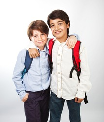 Two cheerful teenagers isolated on white background, happy schoolboys with backpack standing in classroom, best friends hugging indoors, back to school, education and knowledge concept