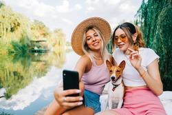 Two cheerful woman friends resting outdoor on lake pier with dog, making photo, selfie