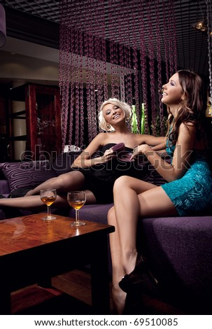 Two cheerful women enjoying an evening - stock photo