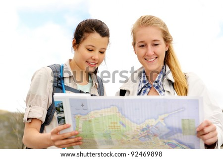 two cheerful women hiking outdoors and consulting their map for the direction in which to travel