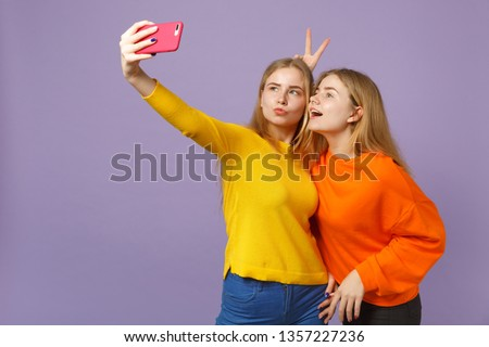 Two cheerful young blonde twins sisters girls in colorful clothes doing selfie shot on mobile phone isolated on pastel violet blue wall background. People family lifestyle concept. Mock up copy space