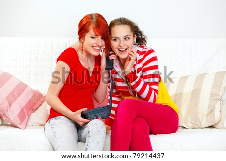 Two cheerful young girlfriends sitting on sofa and talking on phone