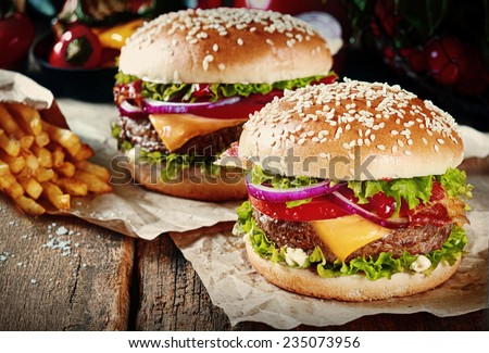 Two cheeseburgers on sesame buns with succulent beef patties and fresh salad ingredients served with French Fries on crumpled brown paper on a rustic wood table