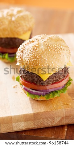 two cheeseburgers on wooden board shot from high angle with vertical aspect ratio.