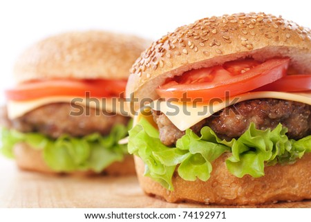 Two cheeseburgers with tomatoes and lettuce on a wooden table