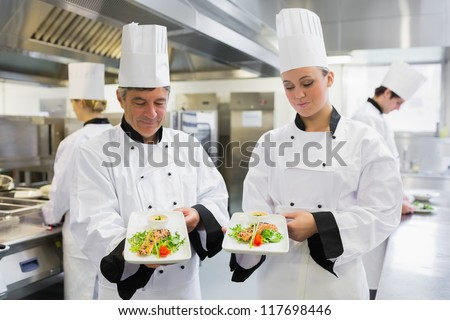 Two Chef's presenting their salmon dishes in the kitchen
