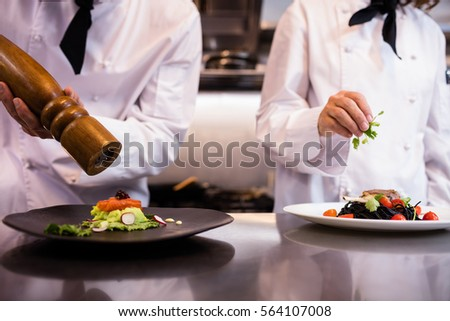 Shutterstock Two chefs garnishing meal on counter in commercial kitchen