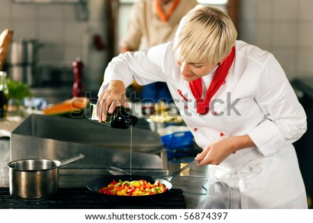 Two chefs in teamwork man and woman in a restaurant or hotel kitchen cooking delicious food she is putting olive oil in the ratatouille