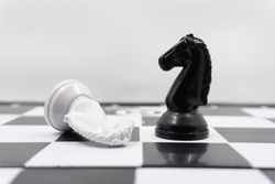 two chess knights with the vanquished white chess piece lying on its side and the black knight standing upright signifying success. There is a white background for placing posts