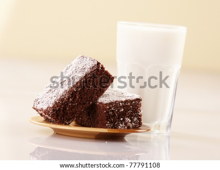 Two chewy chocolate brownies squares and a glass of milk