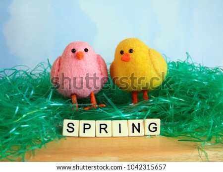 two chicks pink and yellow on green Easter grass and wood with the words spring spelled out in front of the chicks on a sky and clouds background #1042315657