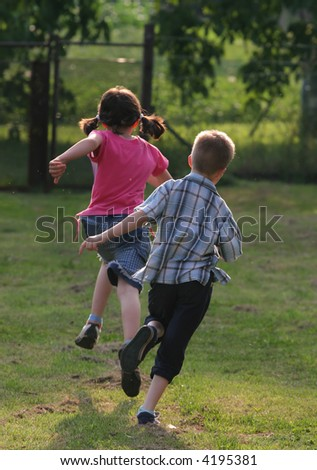 Two child are running in the garden