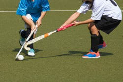 Two child field hockey players. Attacker in blue jersey dekes defender in white and gets past her or him