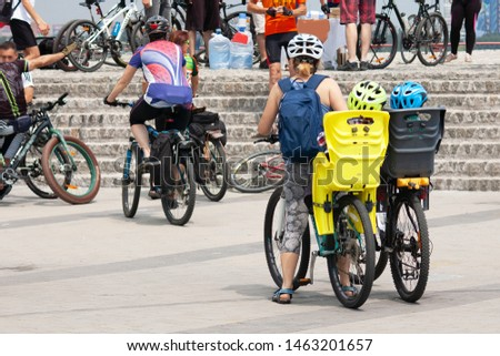 two child sits in child's seats and bike security helmet with mother in bycicle competition, children sport equipment chairs and helmets for cycling concept