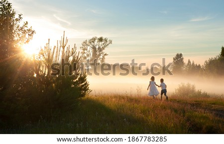 Two children a boy and a girl in white clothes run through a Sunny glade at sunset. Fog, summer time, childhood ストックフォト ©