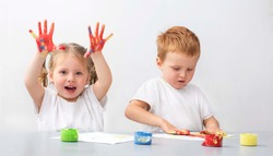 Two children - a boy and a girl - playing with finger paints - hands in colours -sensory therapy at autism
