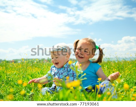 Two children (a girl and a boy) are having fun on green meadow