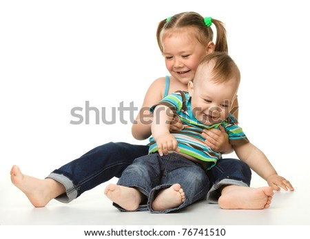 Two children (a girl and a boy) is having fun while sitting on floor, isolated over white