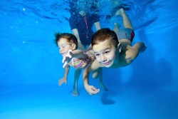 Two children, a small boy and a girl, are engaged in swimming in a children's pool. They play and dive under the water with their eyes open, and a female instructor helps them. Close up. Concept.