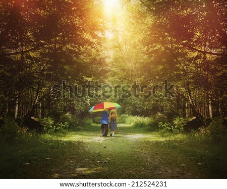 Stock Photo Two children are walking down a sunshine trail in the woods holding a rainbow umbrella for a friendship, hope or happiness concept.