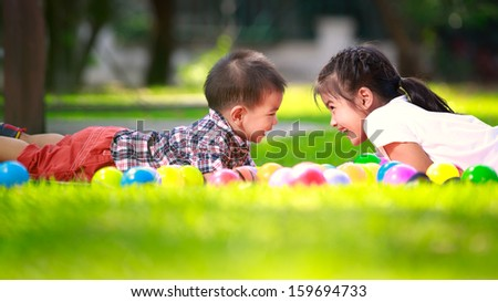 Two children, big syster and her young brother are laying on green grass and smile