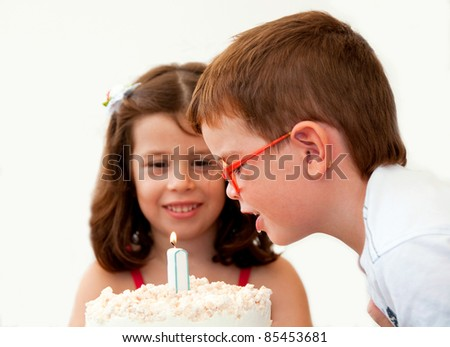 Two children blowing a candle on a birthday cake