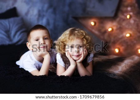 Two children, boy and girl, brother and sister, siblings, laying in bed in loft styled bedroom with star on background. Curly blonde girl and brother. Kids spend time together. Family. Self Isolation. Stock photo ©