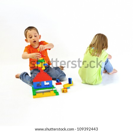 Two children, boy and girl playing with a constructor, but the girl resents and wants to play, isolated on white