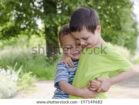 Two children brothers playing and hugging in park in nature.