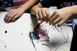 two children build a prototype circuit with a red laser controlled by a microcontroller. STEAM and coding activity