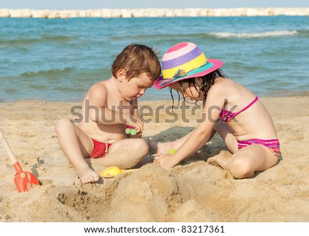 Two children building a sand castle on the beach
