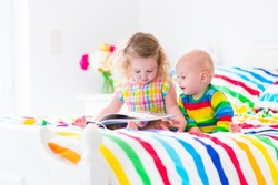 Two children, curly little toddler girl and a funny baby boy, brother and sister, reading a book in a sunny bedroom on a wooden white bed with colorful rainbow bedding enjoying a nice weekend morning