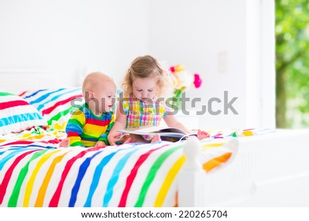 Two children, curly little toddler girl and funny baby boy, brother and sister, reading a book sitting in sunny bedroom on wooden white bed with colorful rainbow bedding enjoying nice weekend morning