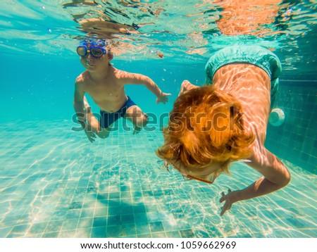 two children diving in masks underwater in pool #1059662969