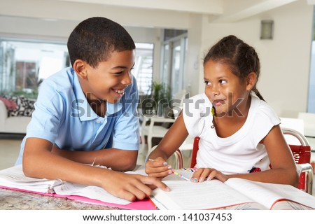 Two Children Doing Homework Together In Kitchen
