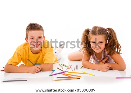 Two children draw with colorful crayons and smile, isolated over white - stock photo