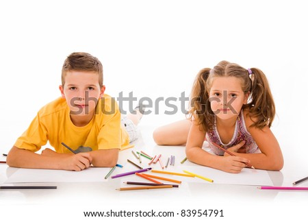 Two children draw with colorful crayons and smile, isolated over white
