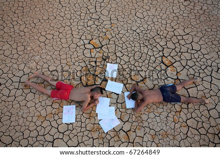 two children drawing flower and leaf on dry land