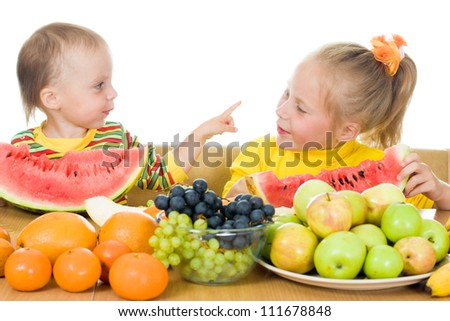Two children eat fruit at a table on a white background,  concept of health care and healthy child nutrition