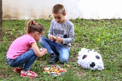 Two children eat sweets candy on the ground in the garden from a broken pinata toy. Girl and boy squat on the grass and unpacking candies. Play and birthday concept. Close up, selective focus
