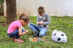 Two children eat sweets candy on the ground in the garden from a broken pinata toy like a football ball. Girl and boy squat on the grass and unpacking candies. Close up, selective focus